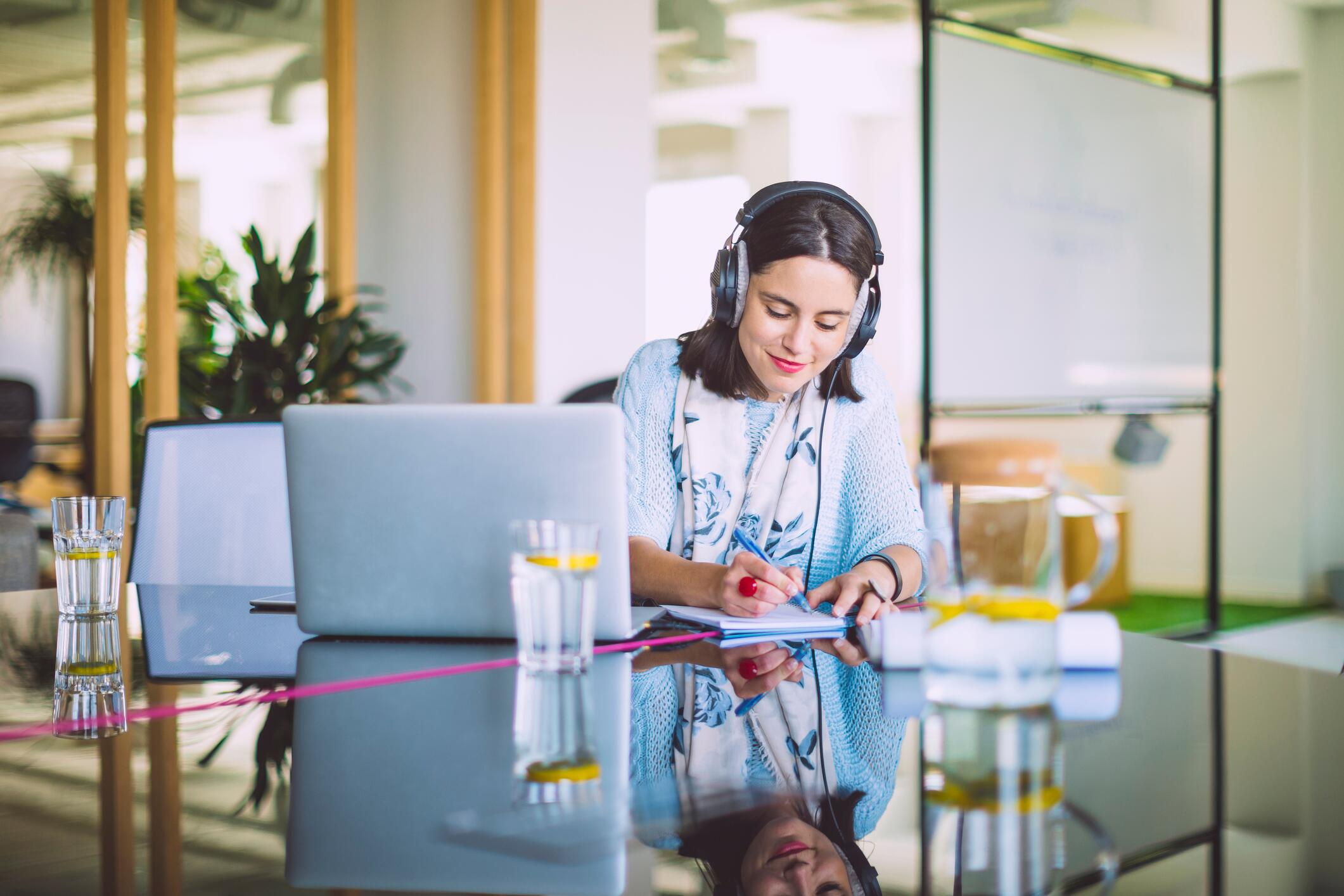 Woman wearing headphones at a computer
