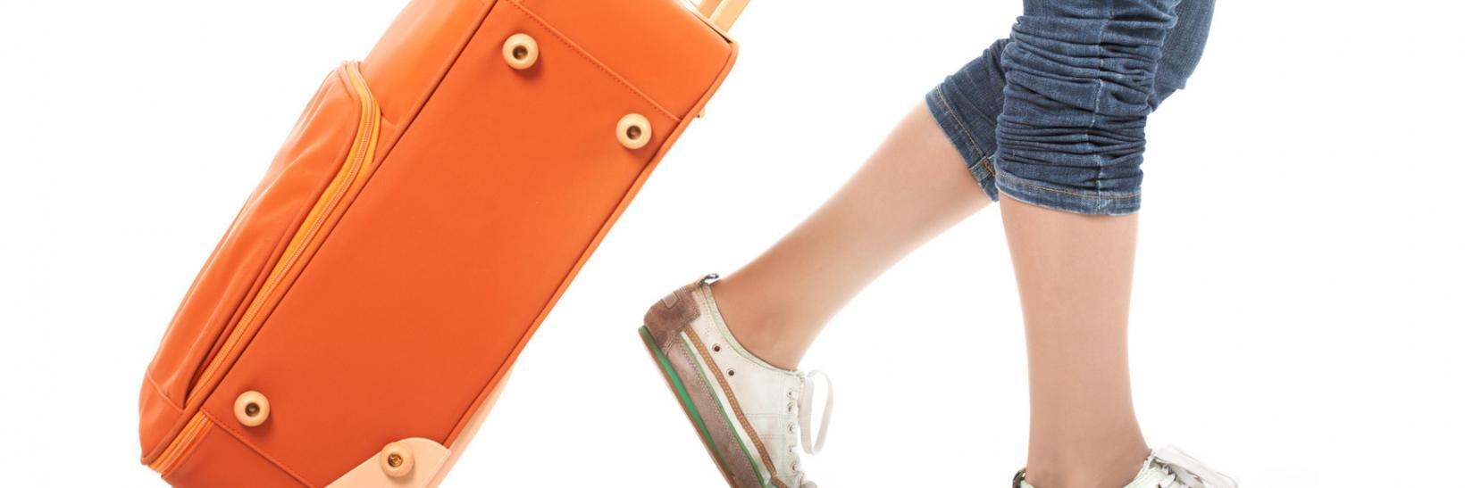 Girl walking with orange suitcase.